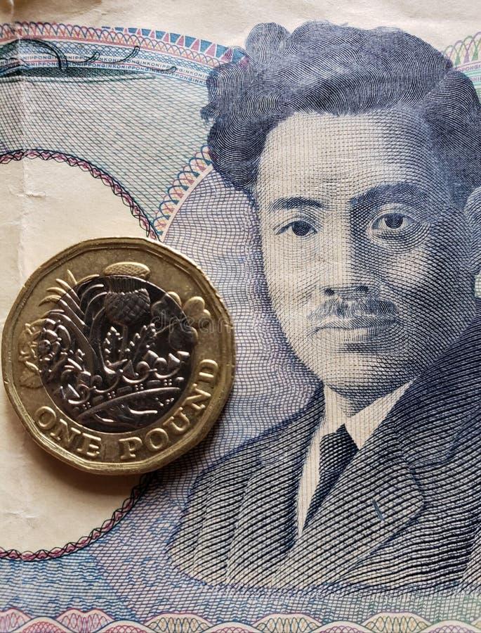 Annäherung an japanische Banknote von 1000 Yen und Münze von einem Sterlingpfund, von Hintergrund und von Beschaffenheit stockfotos