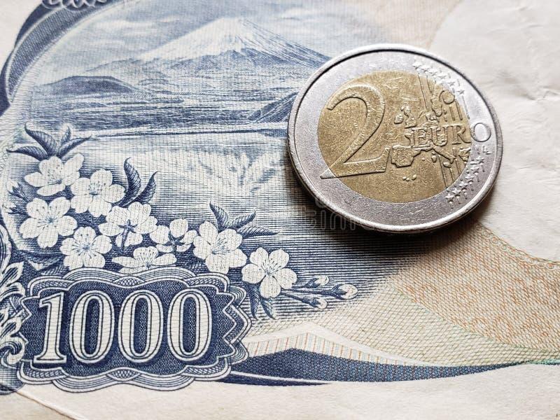 Annäherung an japanische Banknote von 1000 Yen und Münze von 2 Euro, Hintergrund und Beschaffenheit stockfotos
