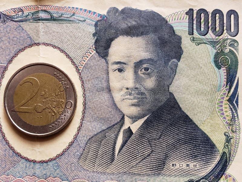 Annäherung an japanische Banknote von 1000 Yen und Münze von 2 Euro, Hintergrund und Beschaffenheit stockfoto