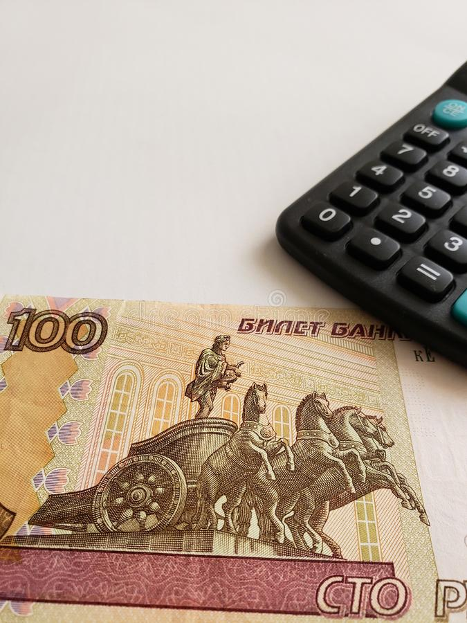 Annäherung an russische Banknote von 100 Rubeln und von Taschenrechner stockbilder