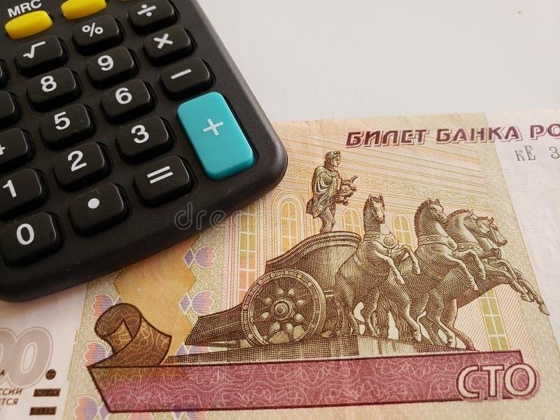 Annäherung an russische Banknote von 100 Rubeln und von Taschenrechner stockfotos
