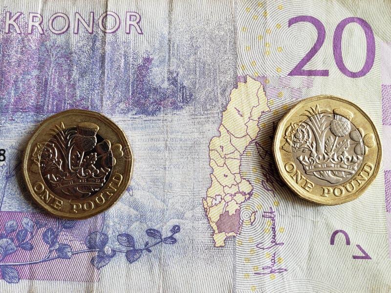 Annäherung an schwedische Banknote von zwanzig Krona und Münzen von einem Sterlingpfund, von Hintergrund und von Beschaffenheit lizenzfreie stockfotografie
