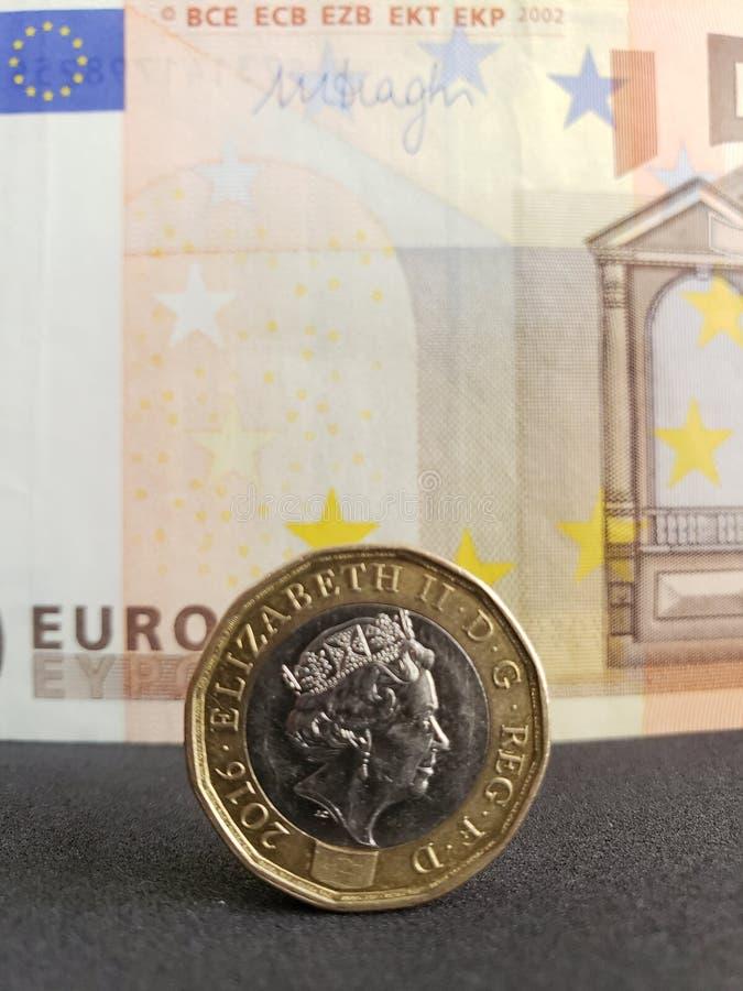 Annäherung, zum von einem Sterlingpfund und von Hintergrund mit europäischer Banknote von Euro fünfzig zu prägen stockbild