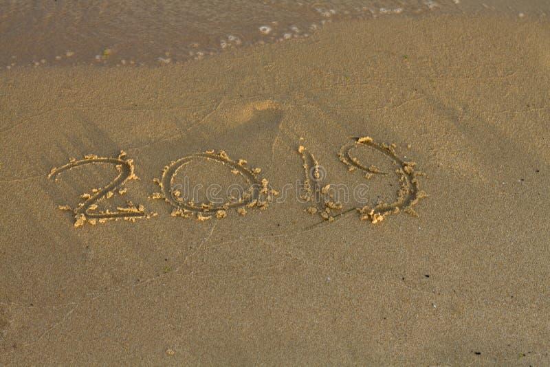 Année 2019 écrite au sable sur une plage de mer photographie stock libre de droits