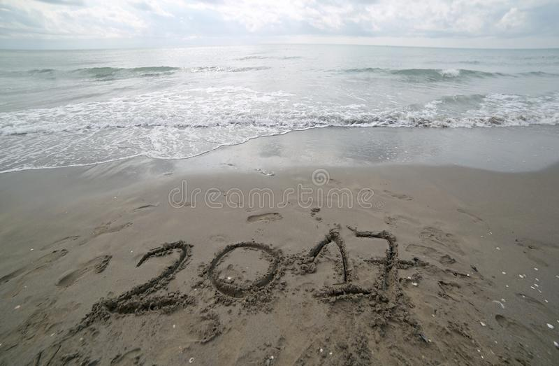 Année 2017 écrite sur le sable de la mer attendant pour être b dégagé photos stock