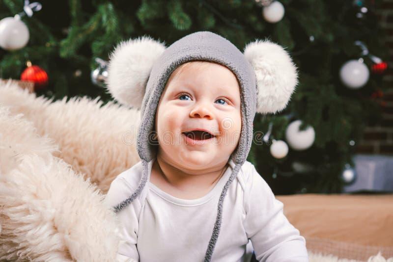 Année de Noël d'enfants de sujet nouvelle Tête se reposante de 1 an d'arbre de Noël de peau d'ours de traîneau de petit bébé garç photo stock