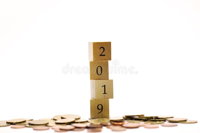 Année 2019 du bloc en bois entourant par la pile des pièces de monnaie images stock