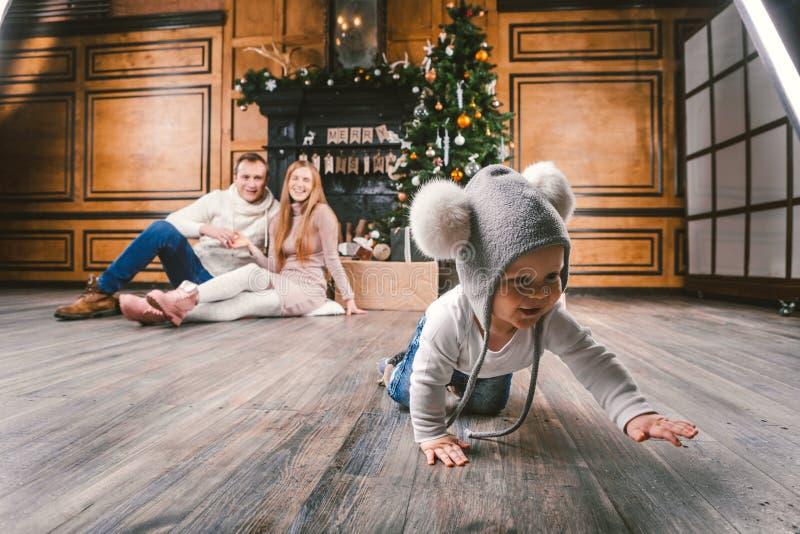 Année et Noël de vacances de famille nouvelle Jeune fils caucasien de papa de maman de famille 1 an reposer le plancher en bois p photos stock