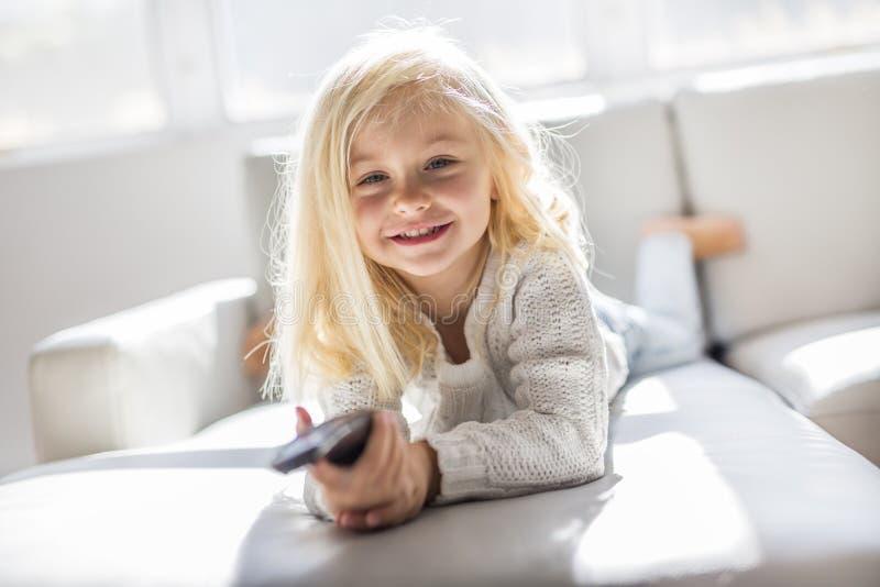 4 années d'enfant regardant la TV fixer sur le sofa à la maison seulement image libre de droits