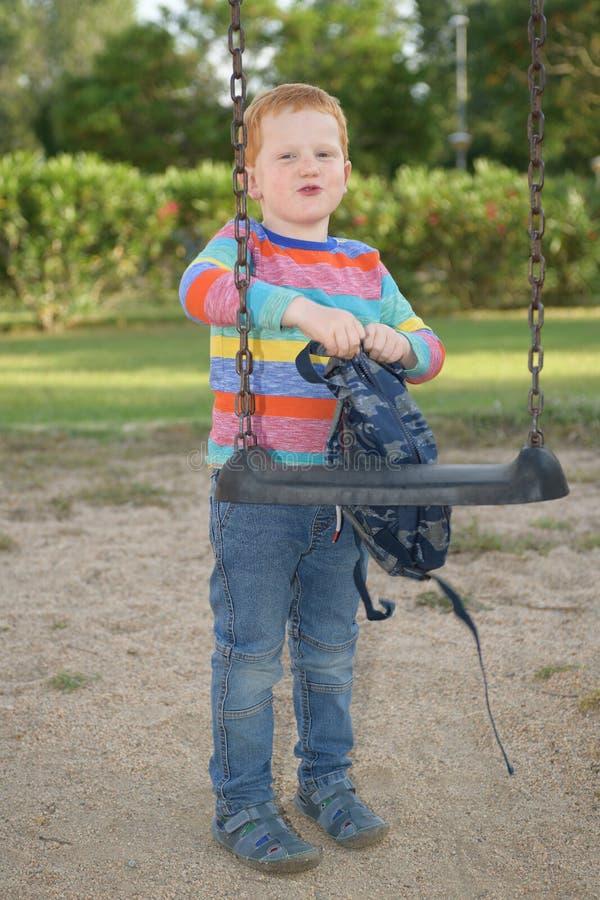 5 années de garçon heureux de roux manipulant son sac à dos sur une oscillation avant d'aller instruire image stock