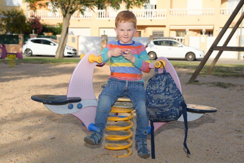 5 années de garçon heureux de roux s'asseyant sur une bascule avant d'aller instruire image libre de droits