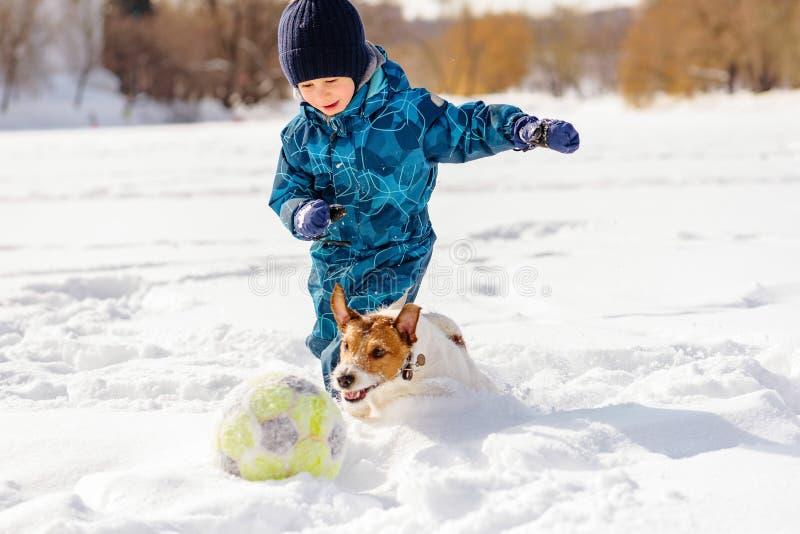 4 années de garçon jouant au football du football avec son chien sur la neige image libre de droits