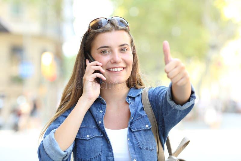 Années de l'adolescence au téléphone faisant des gestes le pouce vers le haut de l'extérieur images stock