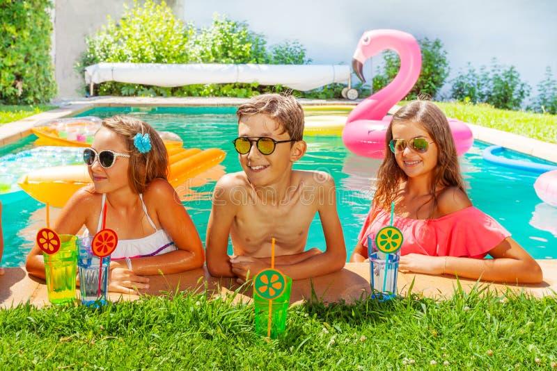 Années de l'adolescence buvant des cocktails détendant dans la piscine photographie stock libre de droits