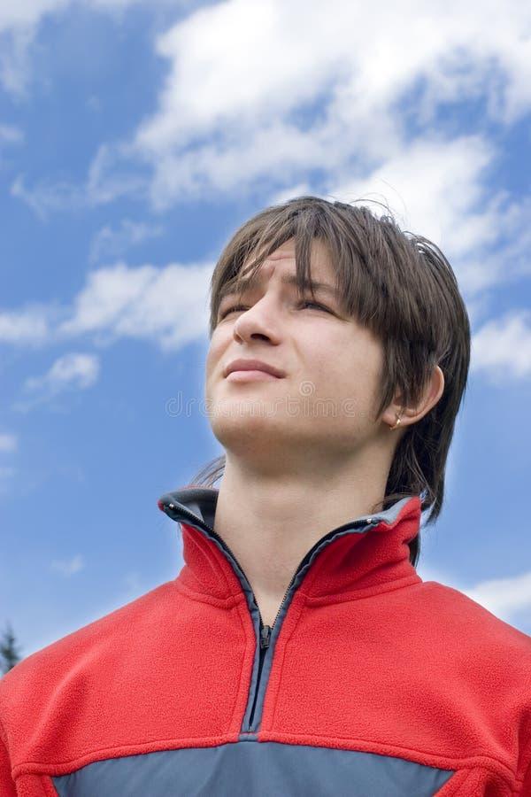 Années de l'adolescence de garçon regardant aux cieux bleus photographie stock