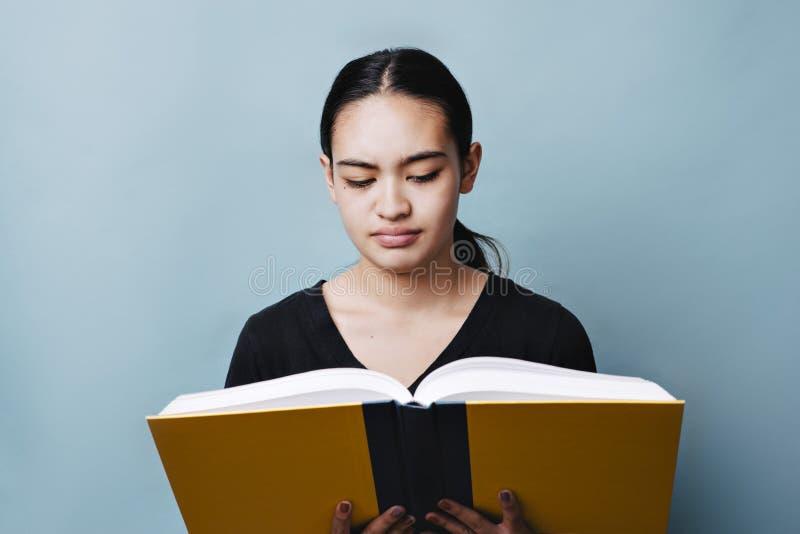 Années de l'adolescence féminines confuses lisant un manuel images libres de droits