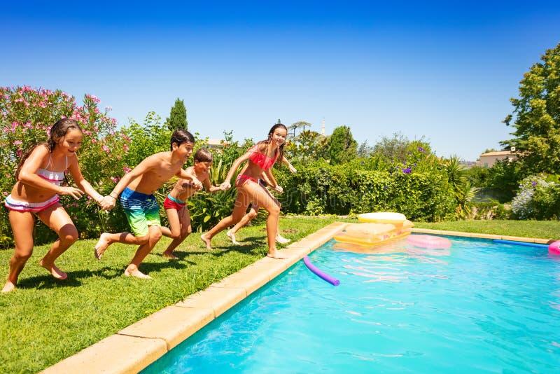 Années de l'adolescence heureuses courant ensemble à la piscine photographie stock libre de droits