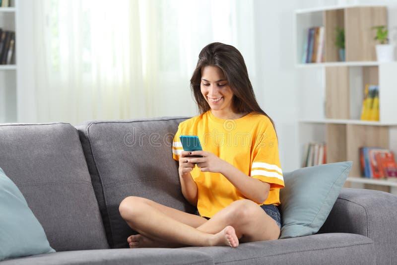 Années de l'adolescence heureuses en jaune utilisant le téléphone à la maison image libre de droits