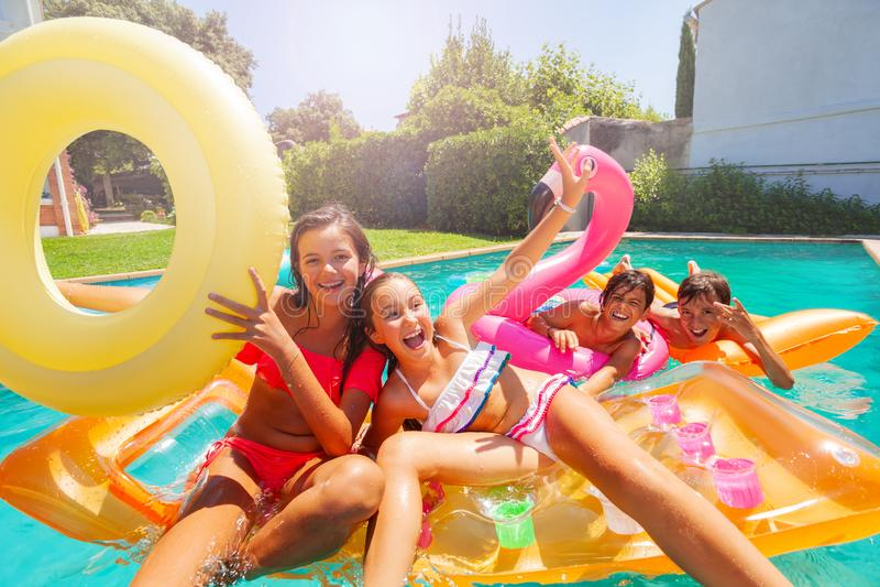 Années de l'adolescence mignonnes jouant avec les flotteurs de natation dans la piscine photographie stock libre de droits