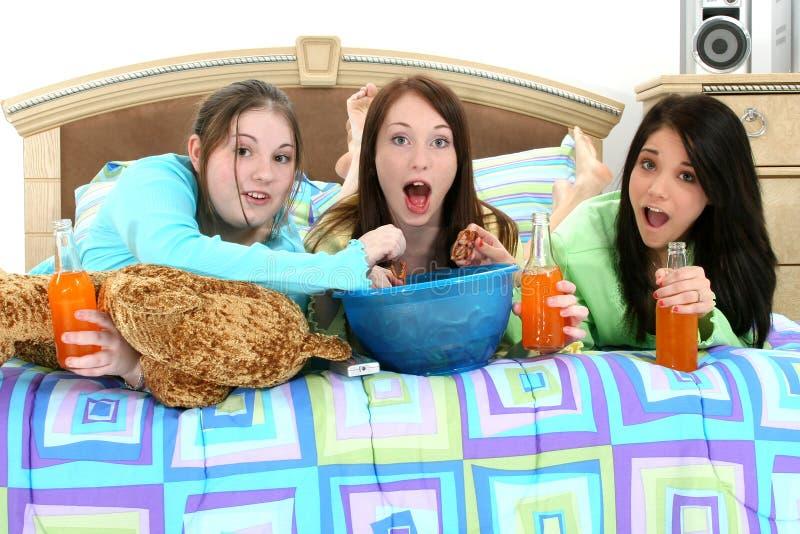 Années de l'adolescence regardant la TV à la maison image libre de droits
