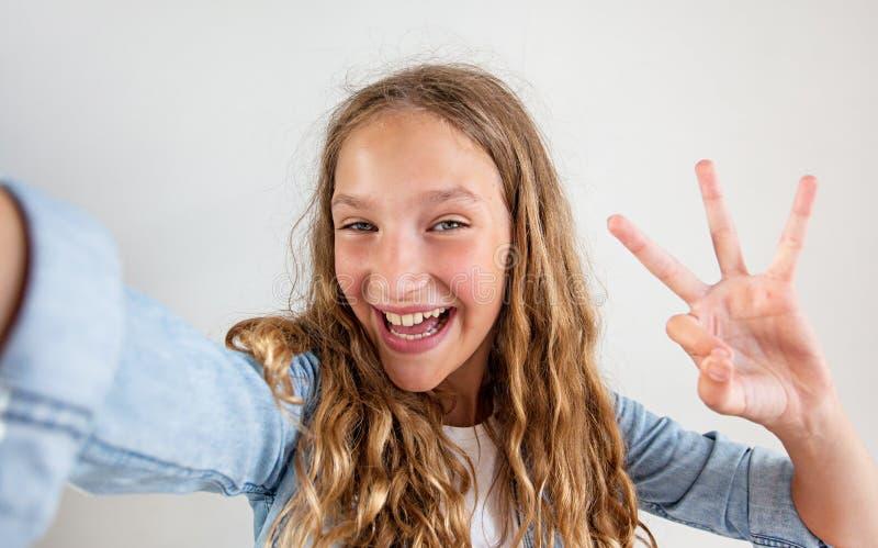 Années de l'adolescence de sourire faisant la photo de selfie sur le smartphone au-dessus de la fille mignonne de fond blanc photos libres de droits