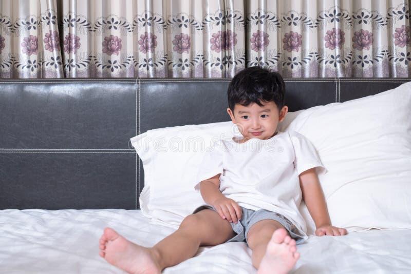 3 années de petit garçon asiatique mignon à la maison sur le lit, le jeu menteur d'enfant et le sourire sur le lit blanc avec l'o images stock