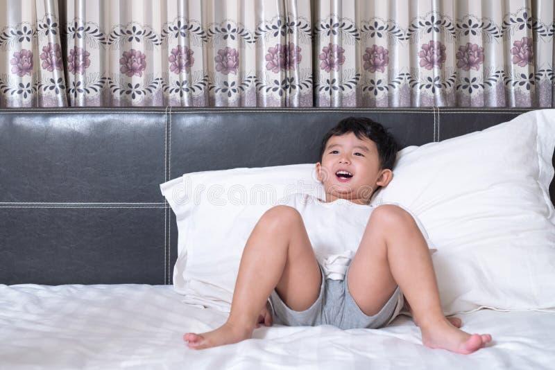 3 années de petit garçon asiatique mignon à la maison sur le lit, mensonge d'enfant photo libre de droits