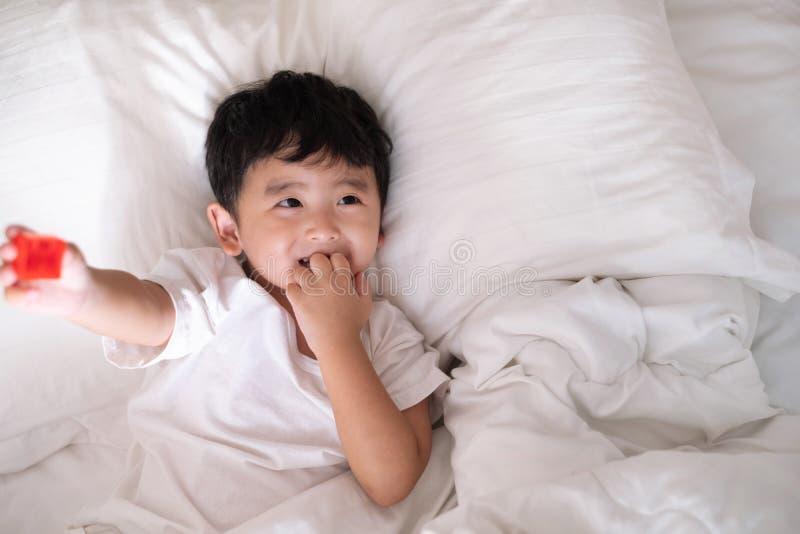 3 années de petit garçon asiatique mignon à la maison sur le lit, mensonge d'enfant images stock