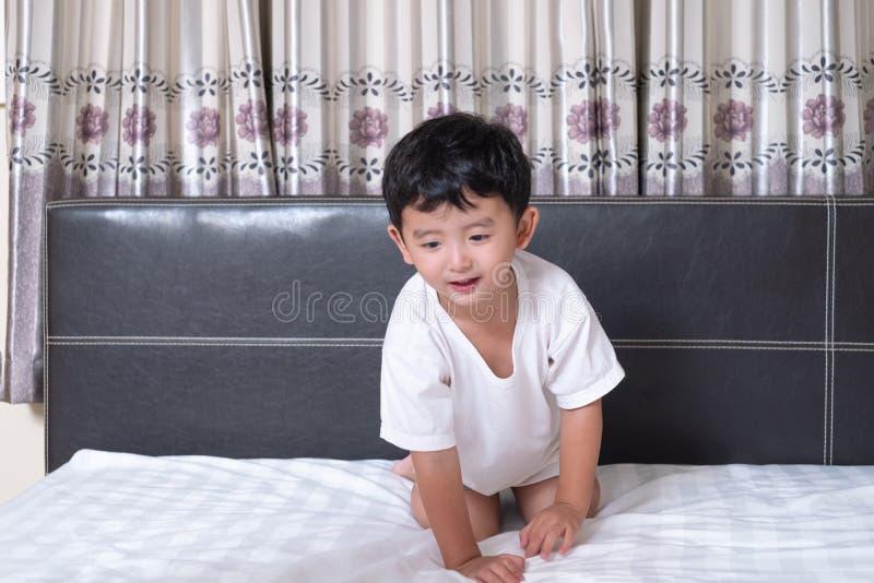3 années de petit garçon asiatique mignon à la maison sur le lit, mensonge d'enfant photographie stock libre de droits