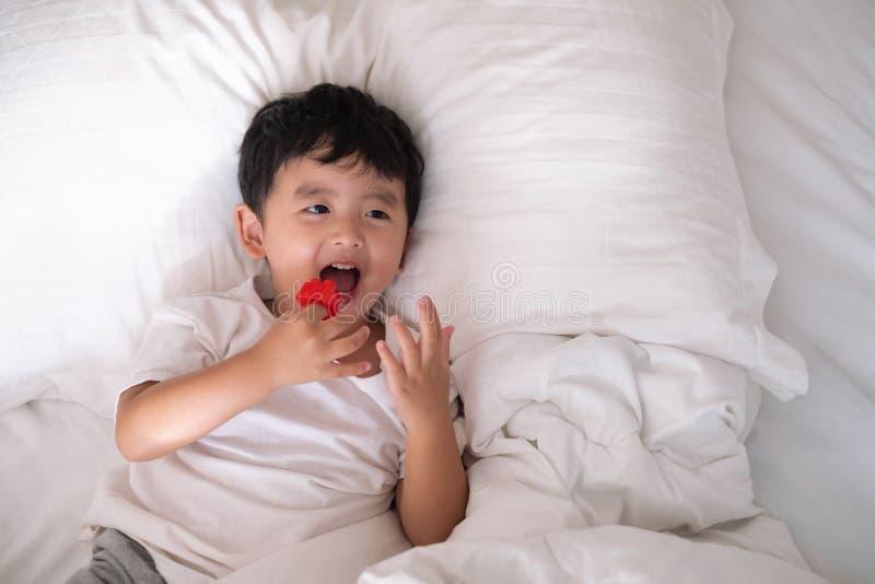 3 années de petit garçon asiatique mignon à la maison sur le lit, mensonge d'enfant image libre de droits