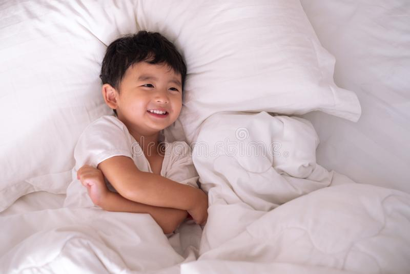 3 années de petit garçon asiatique mignon à la maison sur le lit, mensonge d'enfant image stock