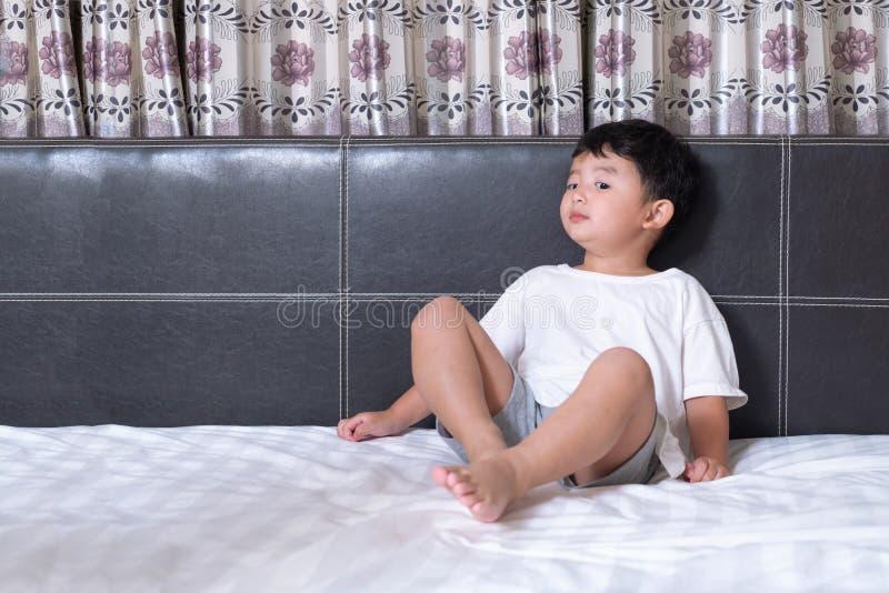 3 années de petit garçon asiatique mignon à la maison sur le lit, mensonge d'enfant photos stock