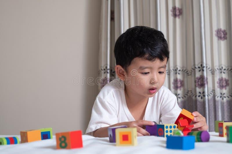 3 années de petit de garçon jouet asiatique mignon de jeu ou puzzle de bloc carré à la maison sur le lit, enfant se trouvant pour image libre de droits