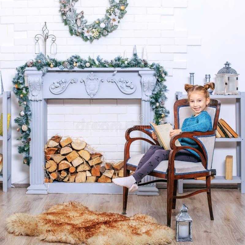 5 années de petite fille de livre de lecture avec des contes d'hiver de Claus place images stock