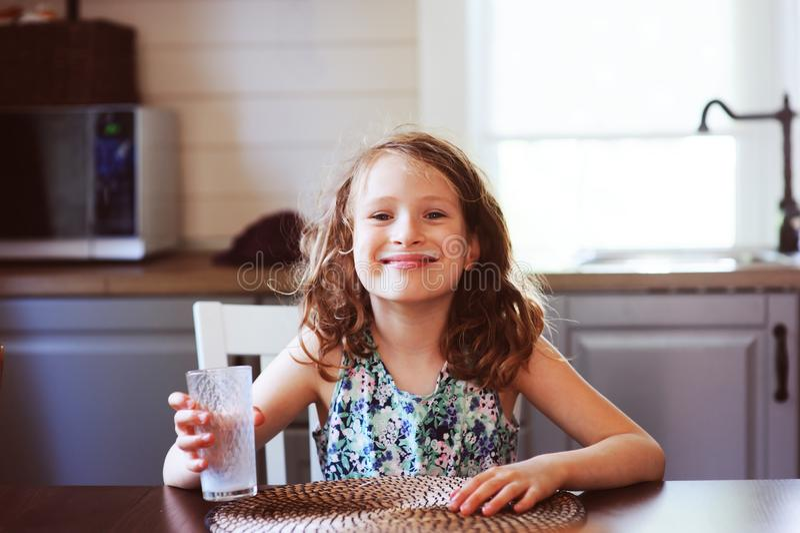 8 années heureuses de fille d'enfant prenant le petit déjeuner dans la cuisine de pays, lait boisson photographie stock