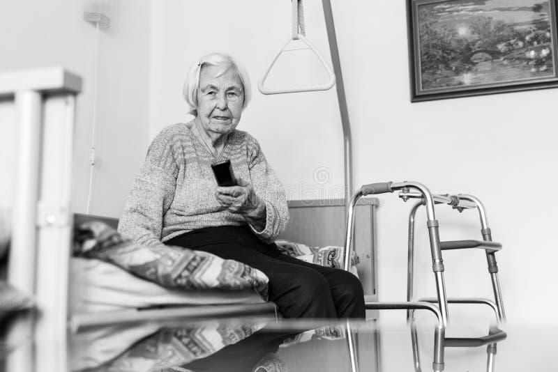 96 années pluses âgé de femme actionnant la TV ou le DVD avec à télécommande photo stock