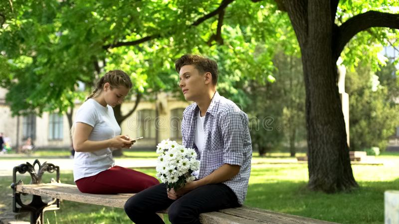 Ann?es de l'adolescence timides avec des fleurs se reposant ? c?t? de la dame, filet surfant au t?l?phone, h?sitation images stock
