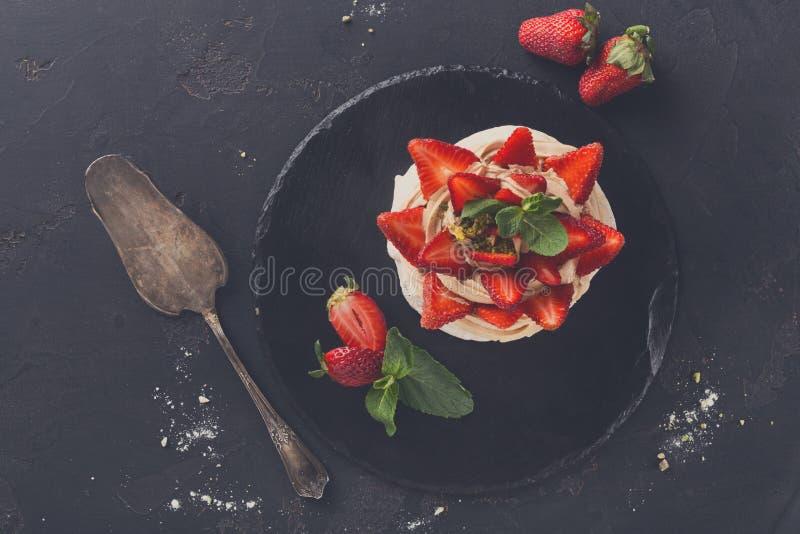 Anna Pavlova-Kuchen mit Erdbeere auf schwarzem Hintergrund stockfotografie