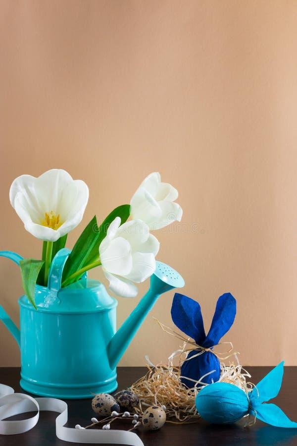 Annaffiatoio blu con i tulipani bianchi e due uova di Pasqua blu nella forma di coniglio su fondo marrone immagini stock libere da diritti