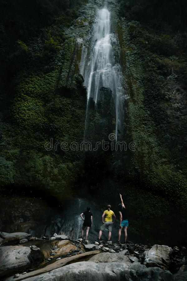 People standing under a waterfall royalty free stock photography