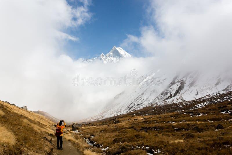 Annapurna, Nepal - 9 de noviembre de 2018: Montaña de fotografía turística Machhapuchhre en el camino al campo bajo de Annapurna, foto de archivo libre de regalías