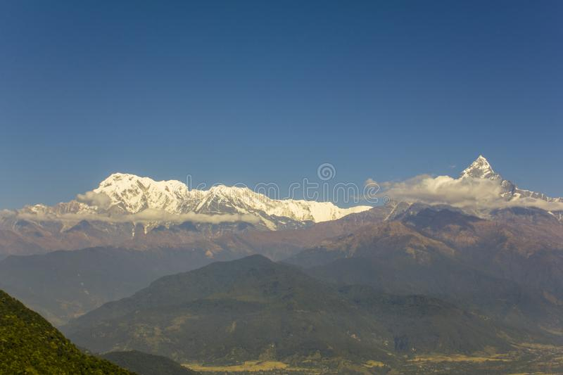 Annapurna snow ridge in a green mountain valley under a clear blue sky. A Annapurna snow ridge in a green mountain valley under a clear blue sky stock image