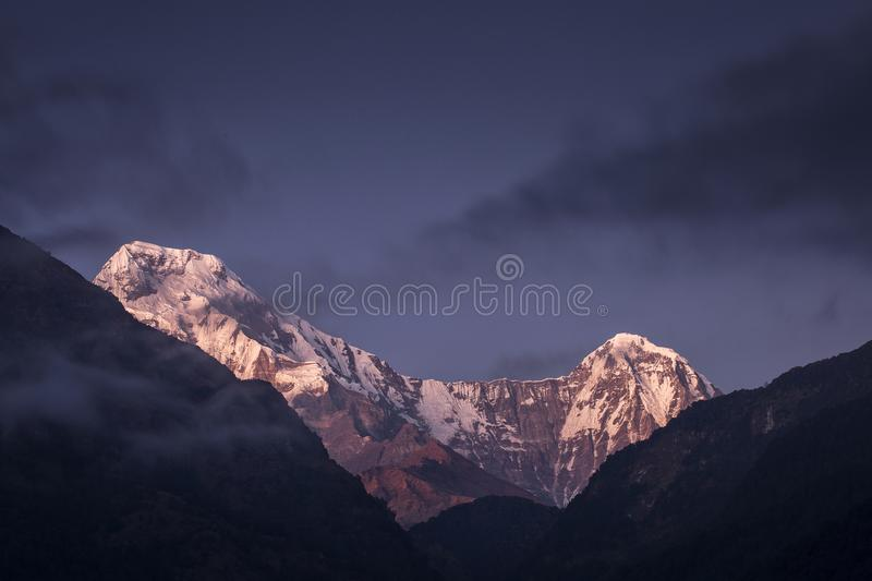 Annapurna South and Hiunchuli at sunset with clouds over. Himalaya Mountain, Nepal. stock photography