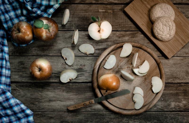 annata frutta mele mature, biscotti, vecchio coltello e un asciugamano di cucina sulla tavola di legno Vista superiore fotografia stock