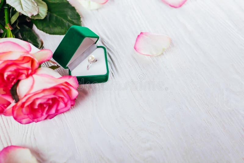 Anneau argenté avec la perle dans le boîte-cadeau et le bouquet verts des roses Présent pour le jour de Valentines photo libre de droits