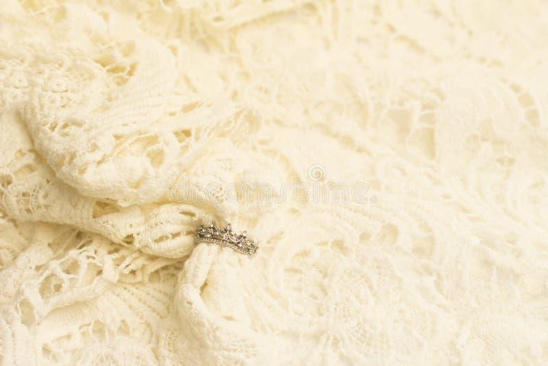 Anneau argenté sur un tissu beige de dentelle photographie stock