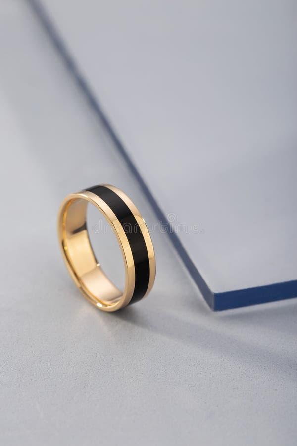 Anneau d'or avec l'émail noir sur le fond bleu photos stock