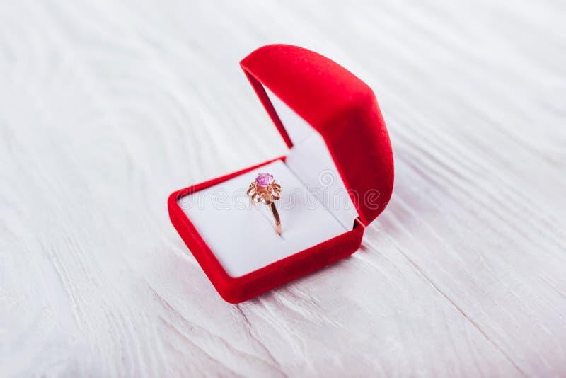 Anneau d'or avec l'améthyste dans le boîte-cadeau rouge sur le fond blanc Présent pour le jour de Valentines image stock