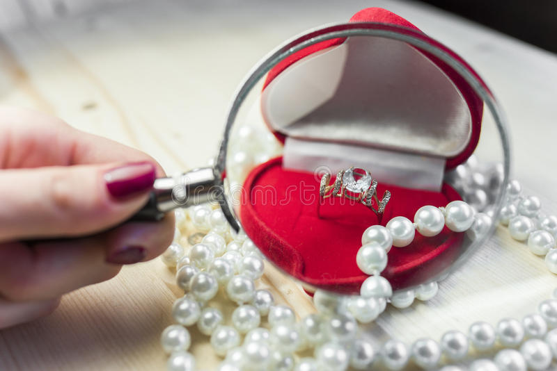 Anneau d'or avec la topaze dans un boîte-cadeau rouge avec des perles au bord de la table image stock