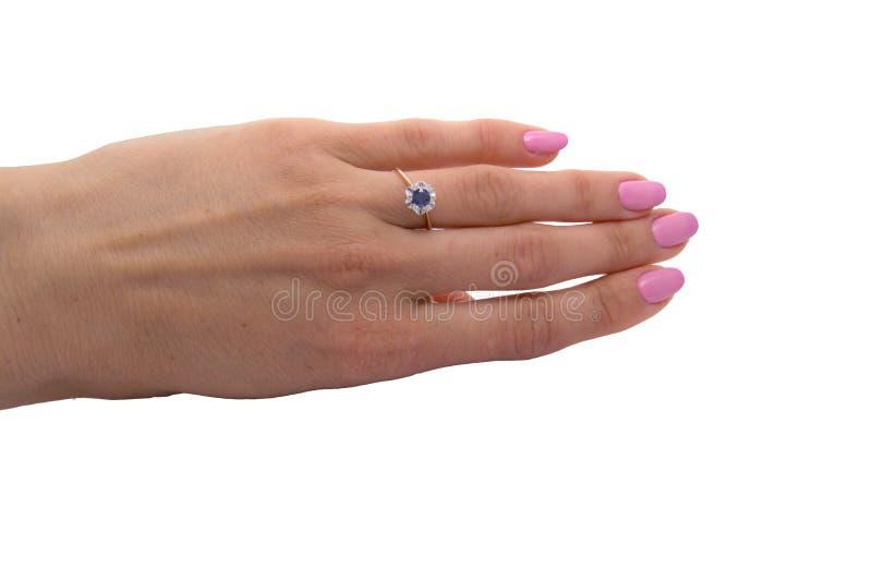 Anneau d'or avec le grand saphir et diamants sur la main du ` s de femme photo stock